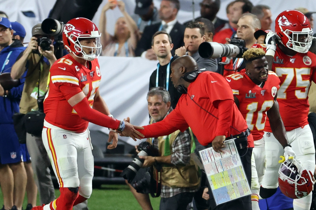 Feb 2, 2020; Miami Gardens, Florida, USA; Kansas City Chiefs quarterback Patrick Mahomes (15) shakes hands with offensive coordinator Eric Bieniemy after a first quarter touchdown against the San Francisco 49ers in Super Bowl LIV at Hard Rock Stadium. Mandatory Credit: Geoff Burke-USA TODAY Sports