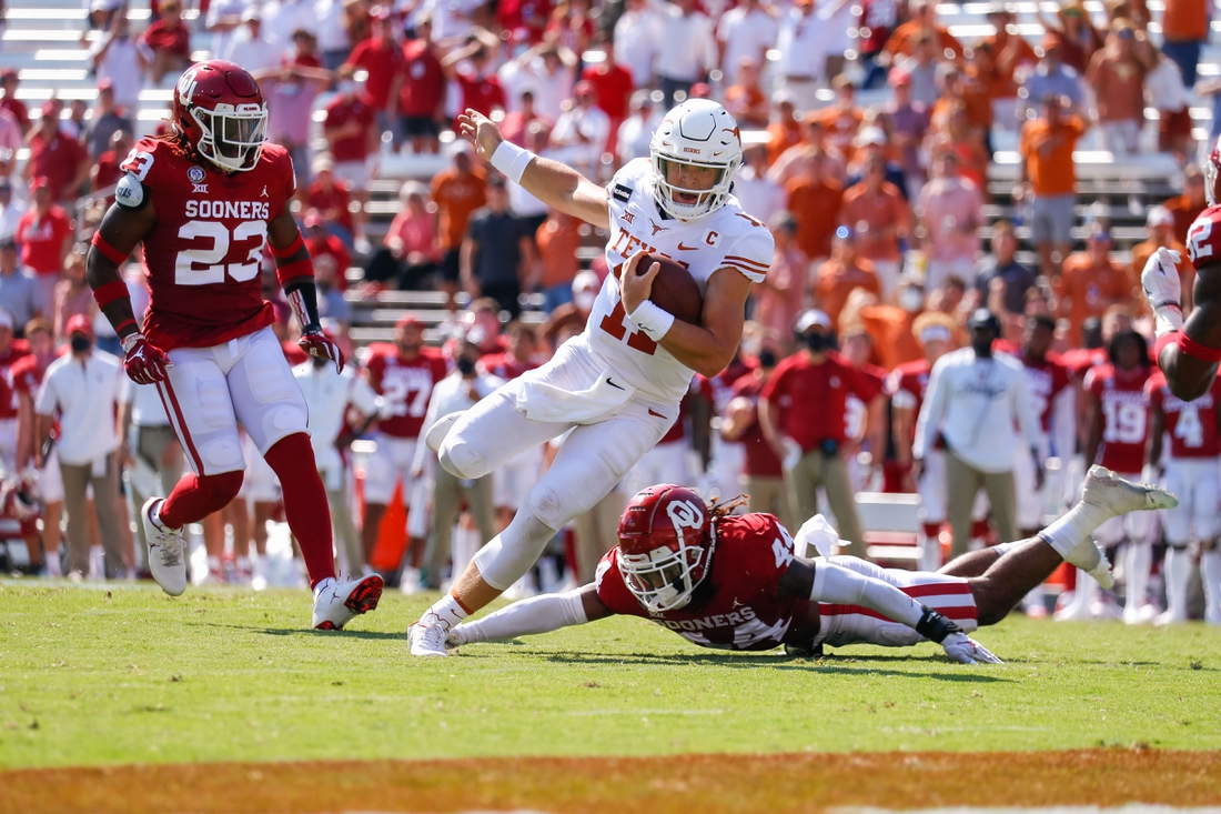 Oct 10, 2020; Dallas, Texas, USA; Texas Longhorns quarterback Sam Ehlinger (11) runs past a tackle attempt by Oklahoma Sooners defensive back Brendan Radley-Hiles (44) during the second quarter of the Red River Showdown at Cotton Bowl. Mandatory Credit: Andrew Dieb-USA TODAY Sports