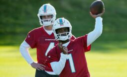Oct 15, 2021; Ware, United Kingdom; Miami Dolphins quarterback Tua Tagovailoa (1) throws the ball as quarterback Reid Sinnett (4) wataches during practice at Hanbury Marriott Manor and Country Club. Mandatory Credit: Kirby Lee-USA TODAY Sports